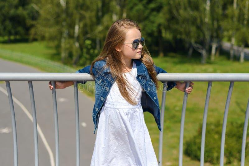 Retrato do vestido bonito do inwhite da menina no revestimento e em óculos de sol azuis da sarja de Nimes imagens de stock