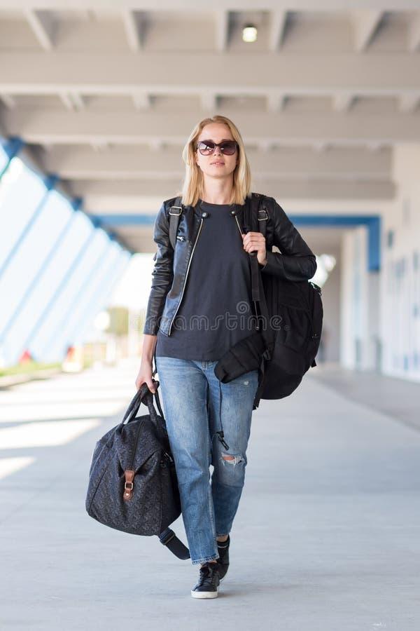 Retrato do viajante fêmea alegre novo que veste a roupa ocasional que leva a trouxa e a bagagem pesadas no aeroporto foto de stock royalty free