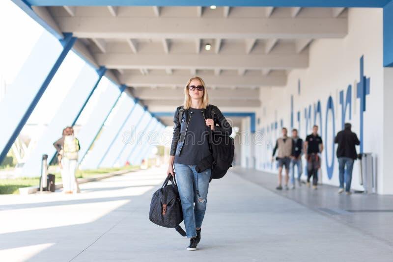 Retrato do viajante fêmea alegre novo que veste a roupa ocasional que leva a trouxa e a bagagem pesadas no aeroporto fotos de stock