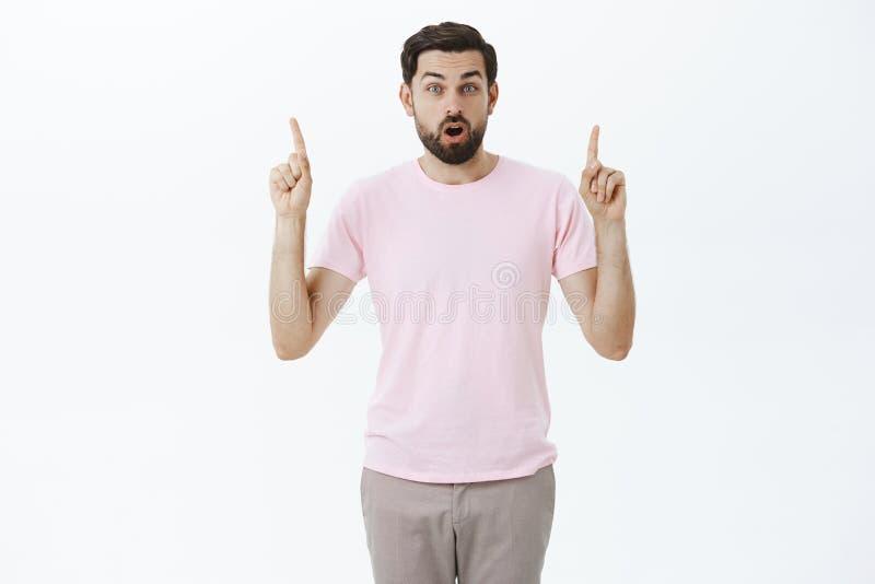 Retrato do visitante masculino bonito surpreendido e impresso no t-shirt ocasional cor-de-rosa que aumenta os indicadores que apo imagens de stock