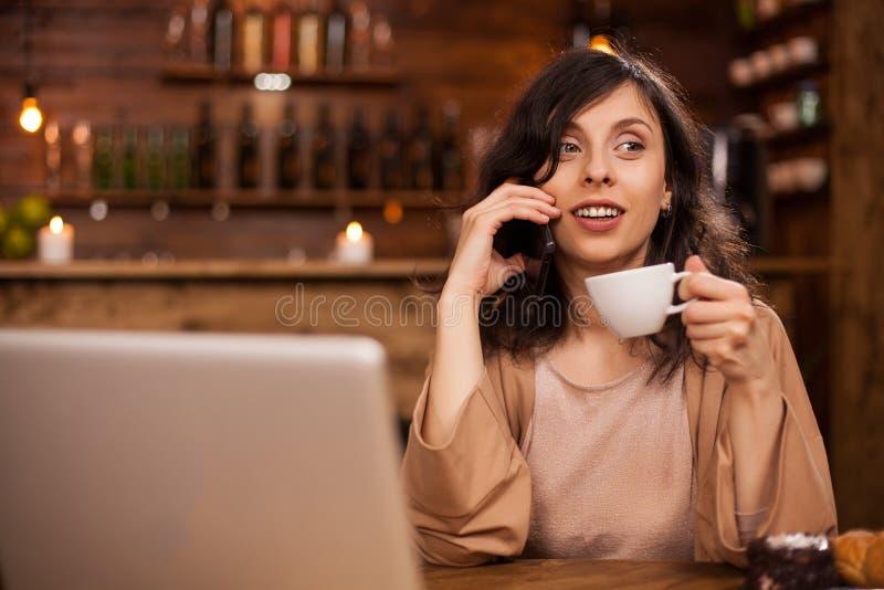 Retrato do womn moderno do negócio em uma cafetaria do moderno que fala no telefone e que guarda uma xícara de café imagens de stock royalty free