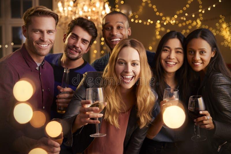 Retrato dos amigos com bebidas que apreciam a festa em casa foto de stock royalty free