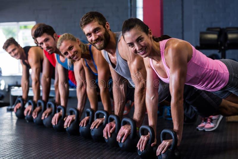 Retrato dos amigos de sorriso que fazem impulso-UPS com kettlebell no gym imagens de stock