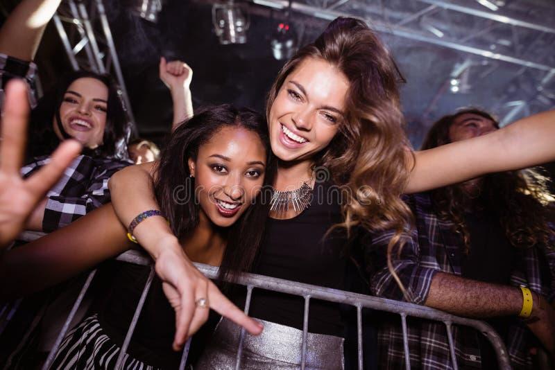 Retrato dos amigos fêmeas alegres que apreciam no clube noturno fotografia de stock royalty free