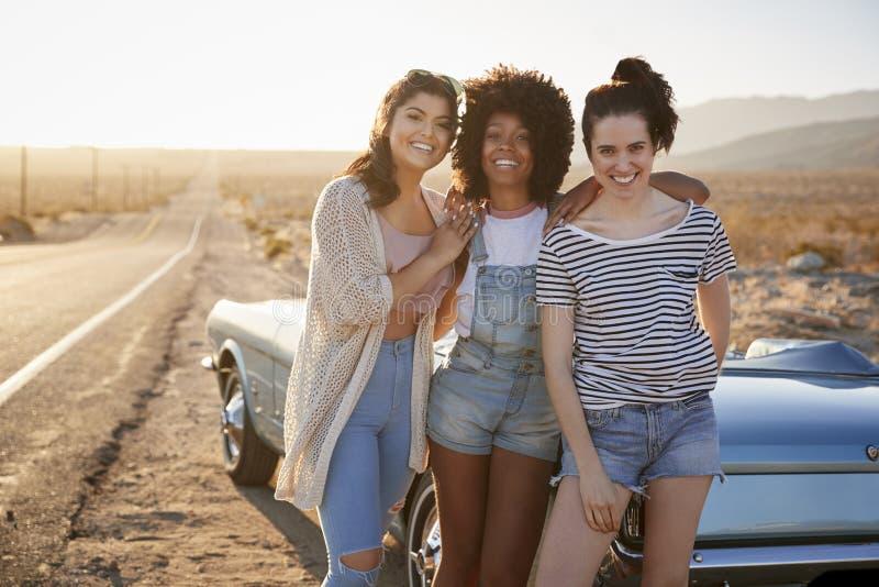 Retrato dos amigos fêmeas que apreciam a viagem por estrada que está ao lado do carro clássico na estrada do deserto foto de stock royalty free