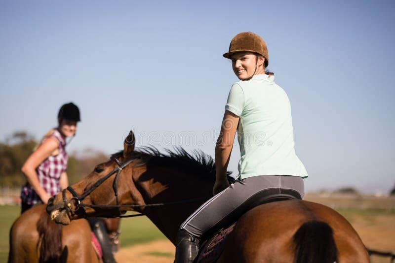 Retrato dos amigos fêmeas que olham sobre o ombro ao sentar-se no cavalo fotografia de stock royalty free