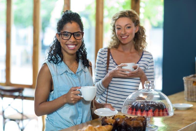 Retrato dos amigos fêmeas que sorriem ao comer o café imagem de stock