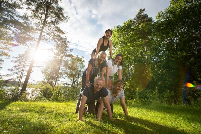 Retrato dos amigos felizes que fazem a pirâmide humana no campo imagem de stock royalty free