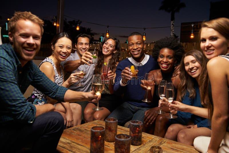 Retrato dos amigos que apreciam a noite para fora na barra do telhado imagens de stock