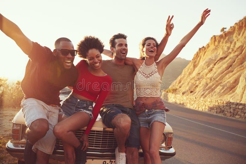 Retrato dos amigos que estão ao lado do carro clássico fotos de stock