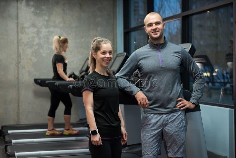 Retrato dos amigos que estão com a mulher que exercita na escada rolante imagens de stock