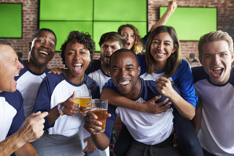 Retrato dos amigos que olham o jogo na barra de esportes em telas imagens de stock royalty free