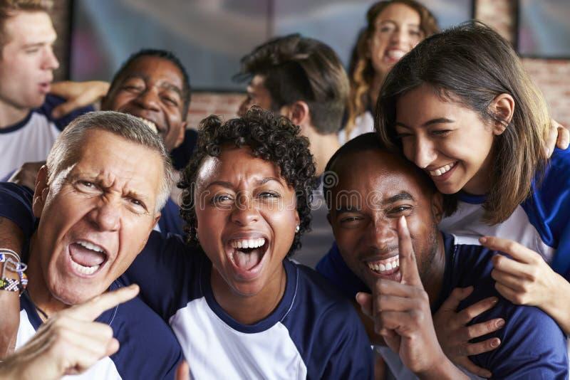 Retrato dos amigos que olham o jogo na barra de esportes em telas fotografia de stock