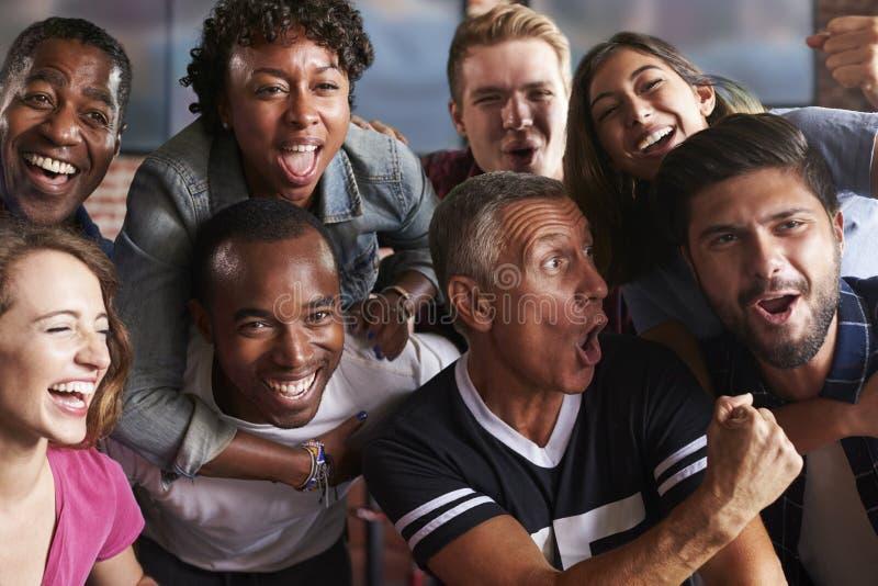 Retrato dos amigos que olham o jogo na barra de esportes em telas imagem de stock