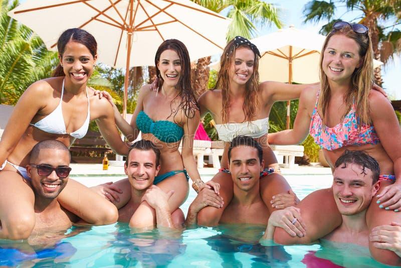 Retrato dos amigos que têm o partido na piscina imagem de stock royalty free