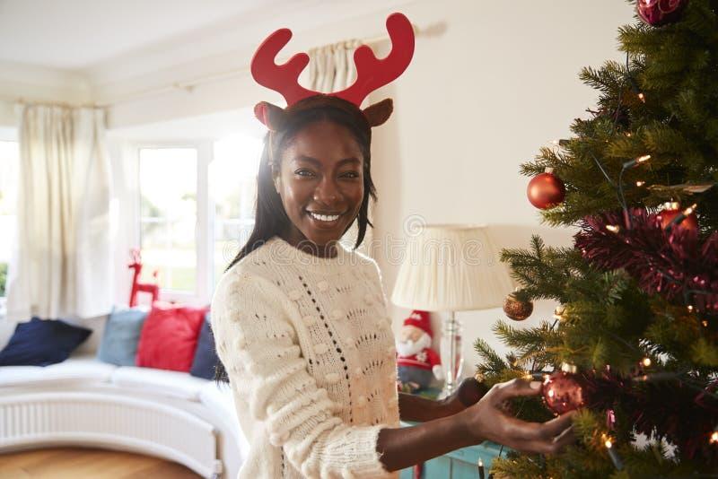 Retrato dos chifres vestindo da mulher que penduram decorações na árvore de Natal em casa fotografia de stock royalty free