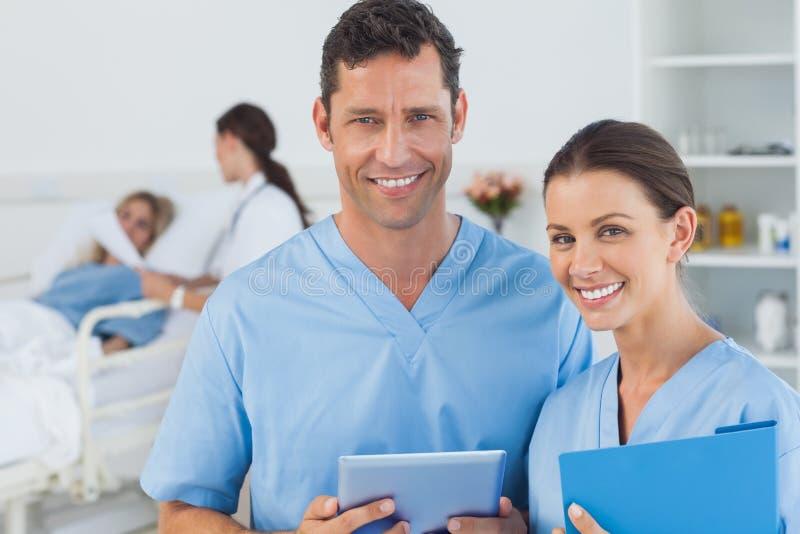Retrato dos cirurgiões com o doutor que atende ao paciente no fundo foto de stock
