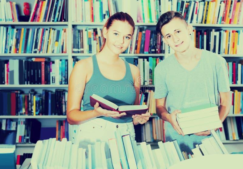 Retrato dos clientes do adolescente e da menina que olham o livro aberto imagens de stock