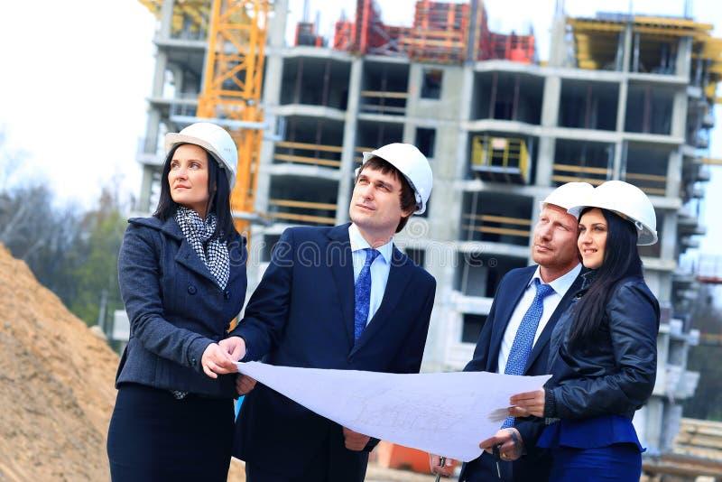 Retrato dos construtores que estão no terreno de construção fotografia de stock royalty free