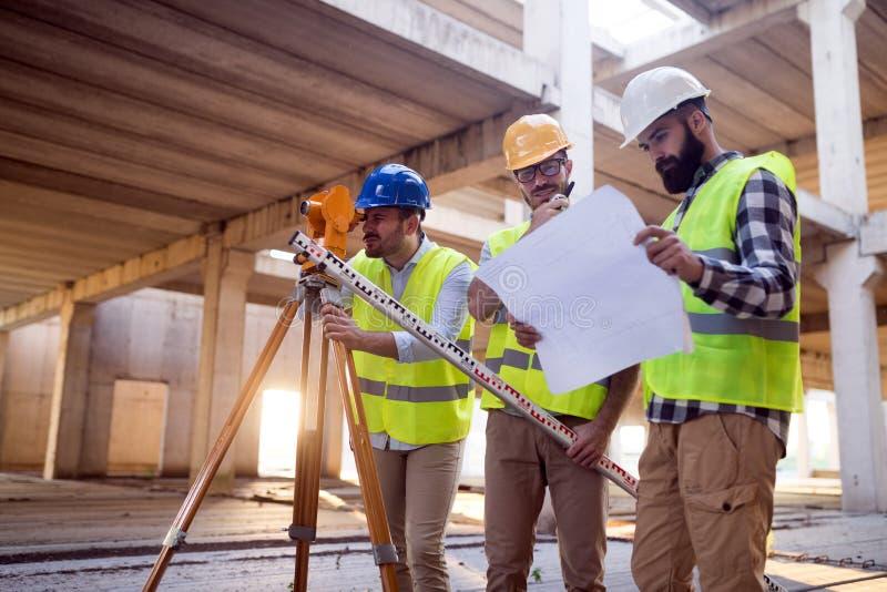 Retrato dos coordenadores de construção que trabalham no terreno de construção imagem de stock