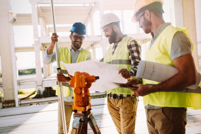 Retrato dos coordenadores de construção que trabalham no terreno de construção fotografia de stock royalty free