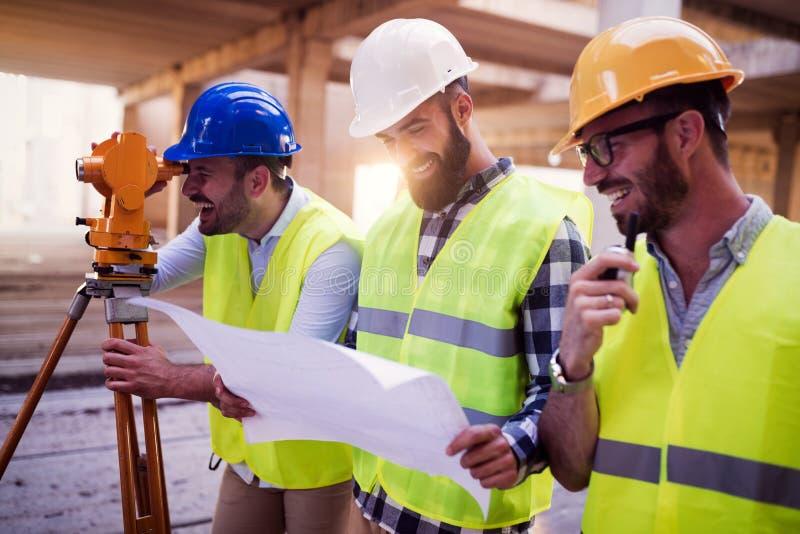 Retrato dos coordenadores de construção que trabalham no terreno de construção imagens de stock royalty free