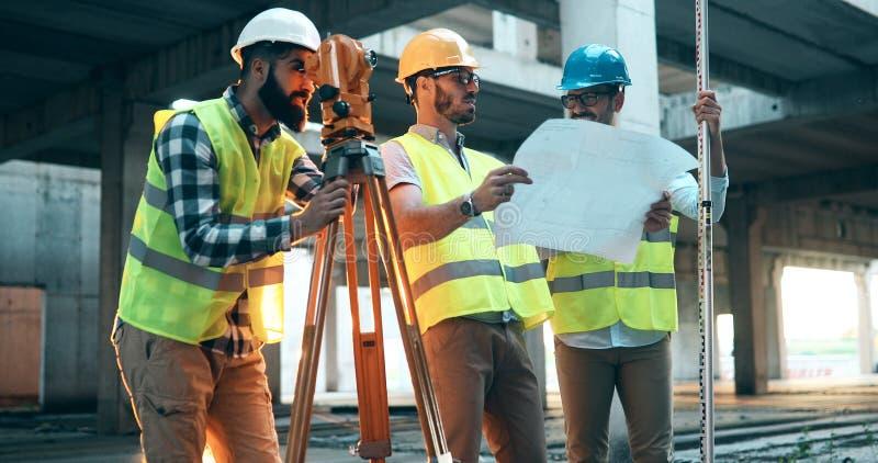 Retrato dos coordenadores de construção que trabalham no terreno de construção fotografia de stock