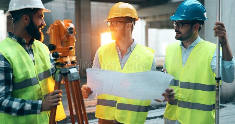Retrato dos coordenadores de construção que trabalham no terreno de construção fotos de stock royalty free