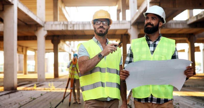 Retrato dos coordenadores de construção que trabalham no terreno de construção fotos de stock