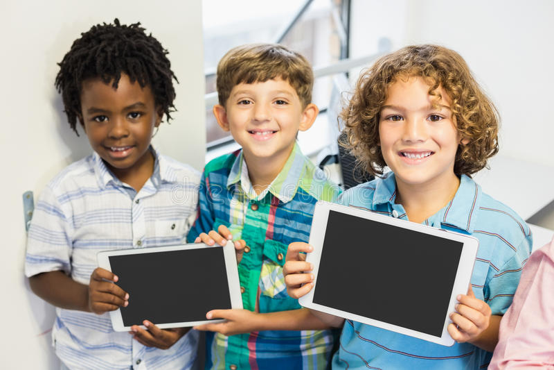 Retrato dos estudantes que guardam a tabuleta digital na sala de aula foto de stock royalty free