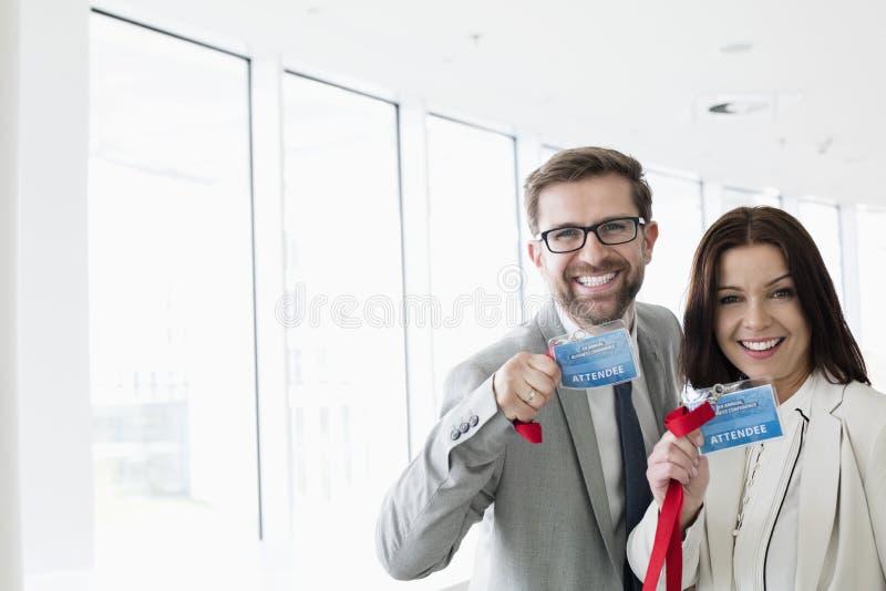 Retrato dos executivos felizes que mostram carteiras de identidade no centro de convenções fotografia de stock