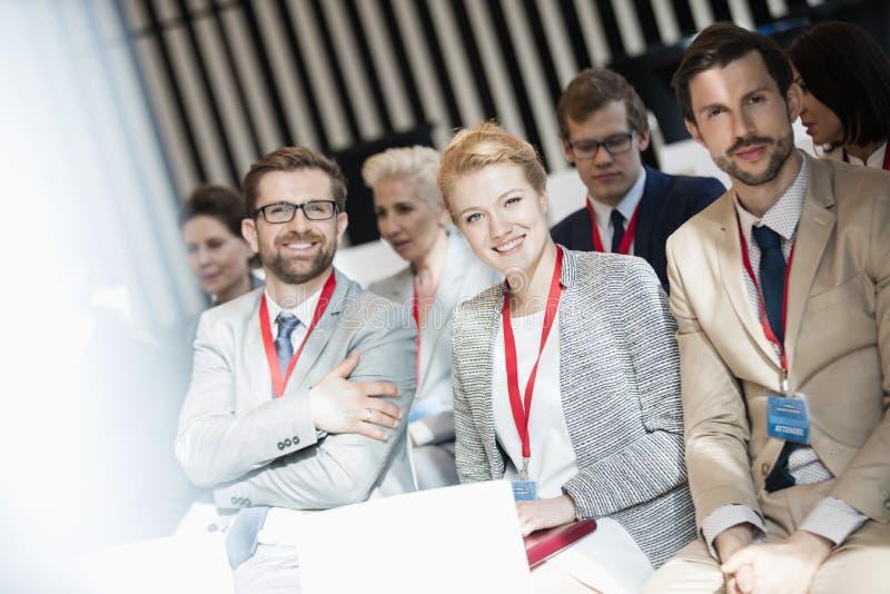 Retrato dos executivos felizes que sentam-se no salão do seminário imagens de stock royalty free