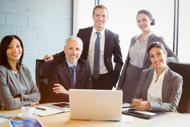Retrato dos executivos que sorriem na sala de conferências fotografia de stock