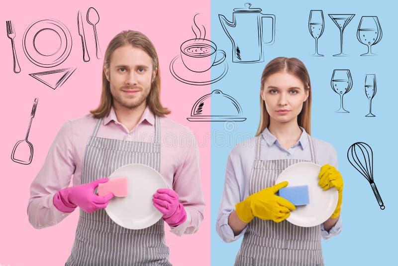 Retrato dos garçons positivos que lavam pratos imagem de stock