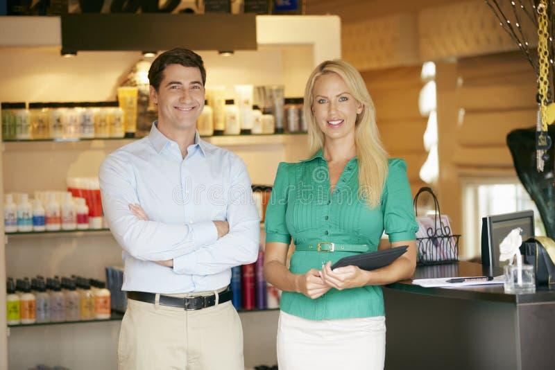Retrato dos gerentes da loja do produto de beleza que guardam a tabuleta de Digitas fotos de stock