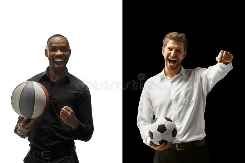 Retrato dos homens de sorriso que guardam a bola do futebol e do basquetebol isolada em um fundo branco e preto foto de stock