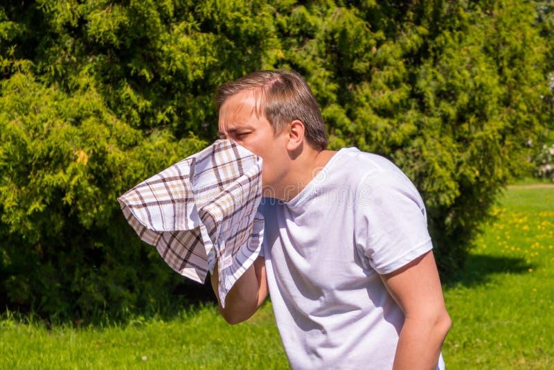 Retrato dos homens que espirram da alergia, em um t-shirt branco, suportes no parque fotos de stock royalty free