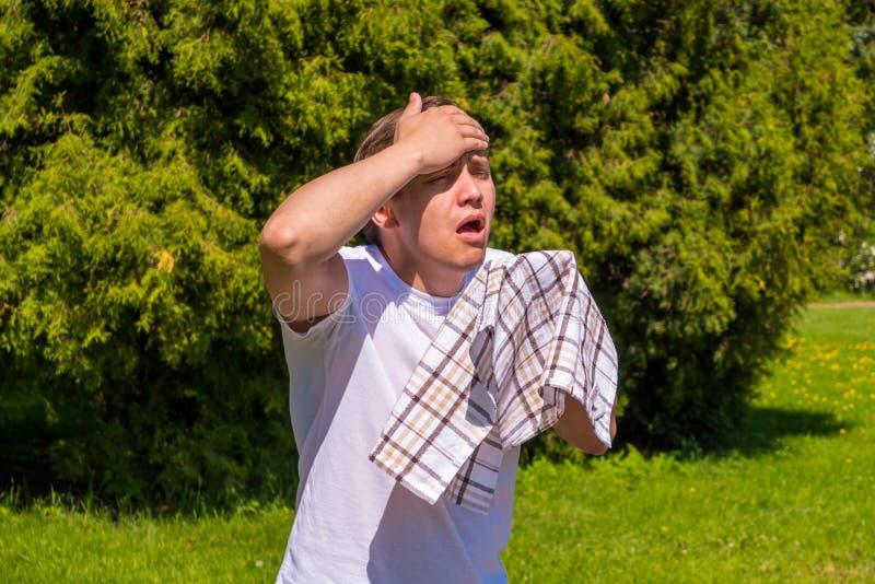 Retrato dos homens que espirram da alergia, em um t-shirt branco, suportes no parque fotografia de stock royalty free