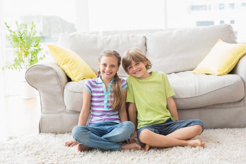 Retrato dos irmãos felizes que sentam-se no tapete na sala de visitas imagens de stock