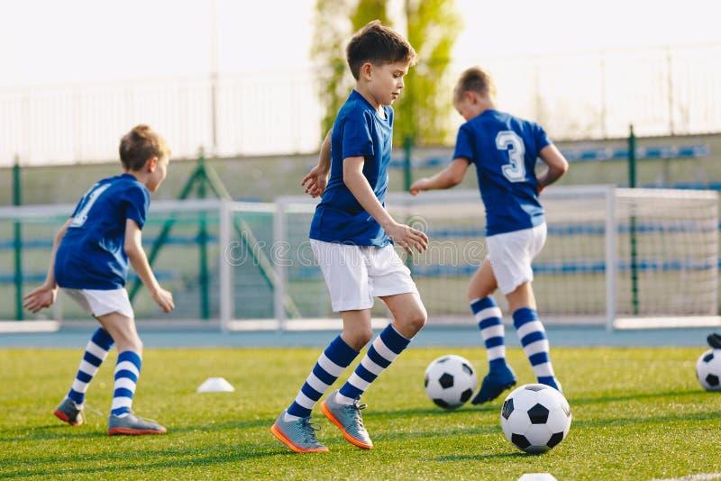 Retrato dos meninos em bola principal da equipe de futebol j?nior da juventude entre cones durante a pr?tica que treinam no campo foto de stock