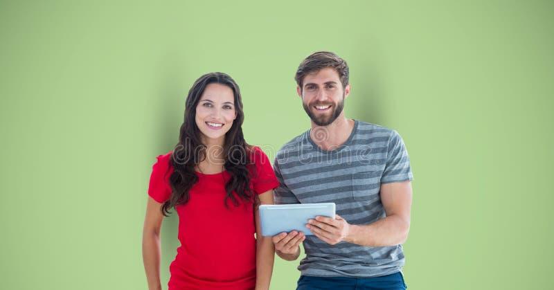 Retrato dos modernos masculinos e fêmeas com a tabuleta digital contra o fundo verde foto de stock royalty free
