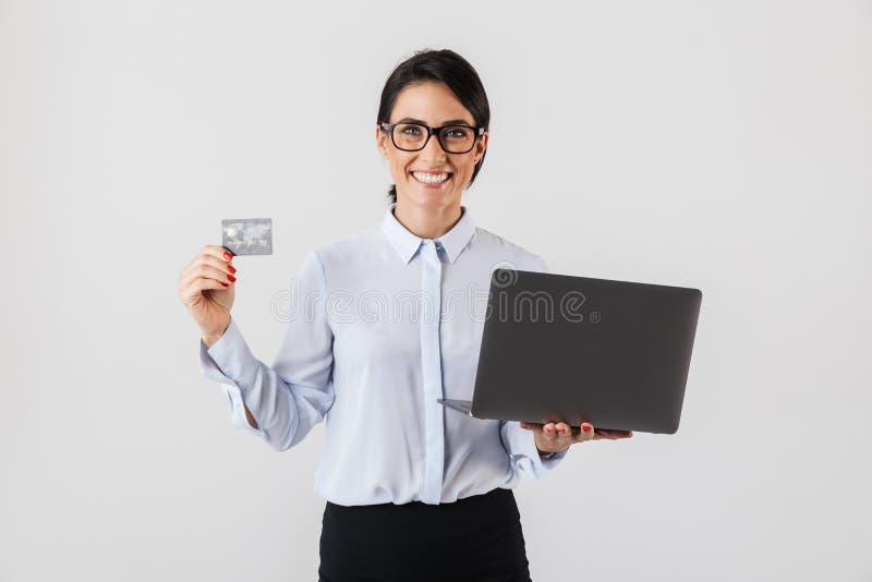 Retrato dos monóculos vestindo de sorriso da mulher de negócios que guardam o cartão de prata do portátil e de crédito no escritó imagens de stock royalty free
