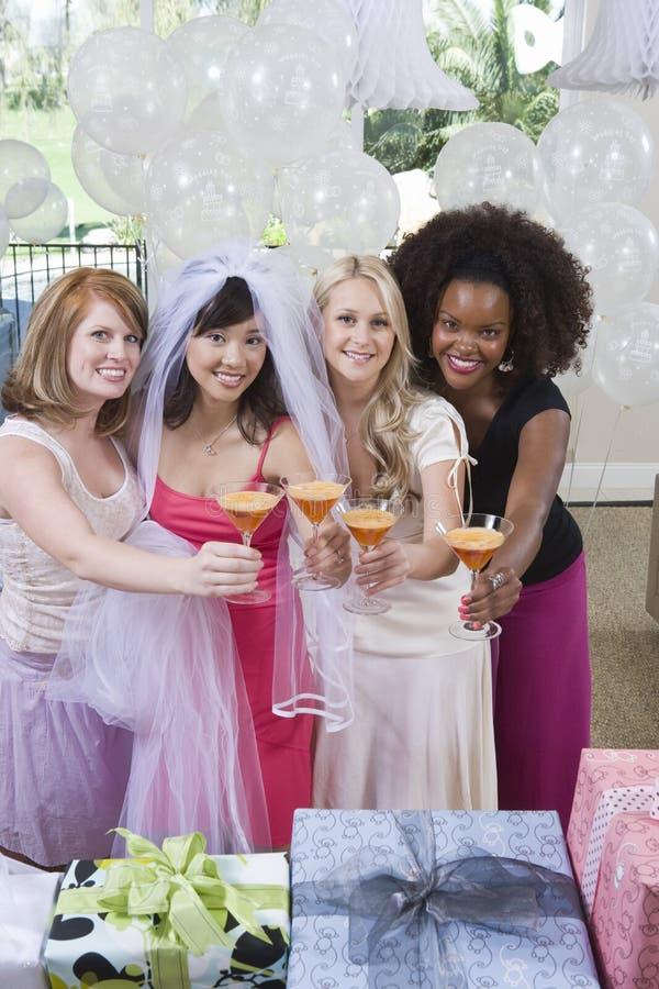 Retrato dos multi amigos étnicos felizes que guardaram vidros de cocktail em Hen Party fotografia de stock