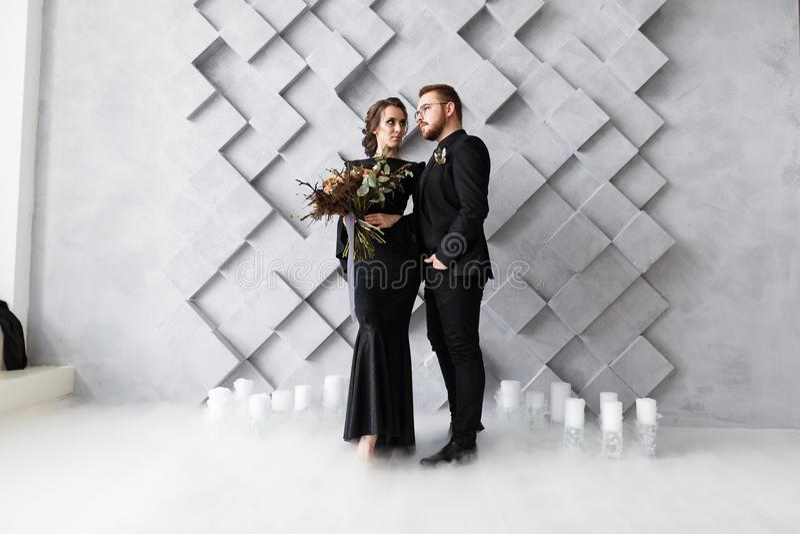 Retrato dos noivos no estúdio Isolado no fundo geométrico cinzento Fumo do gelo seco no assoalho fotografia de stock royalty free