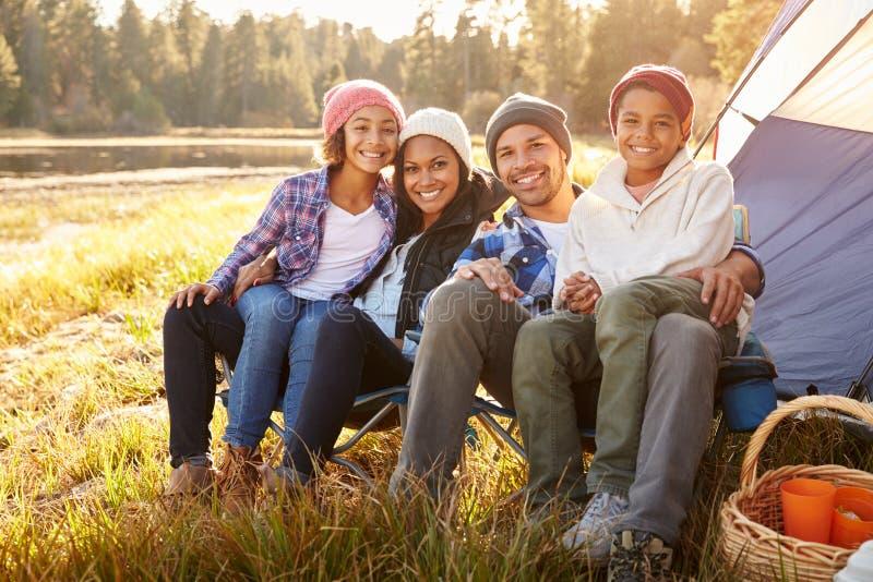 Retrato dos pais com as crianças que acampam pelo lago fotografia de stock royalty free