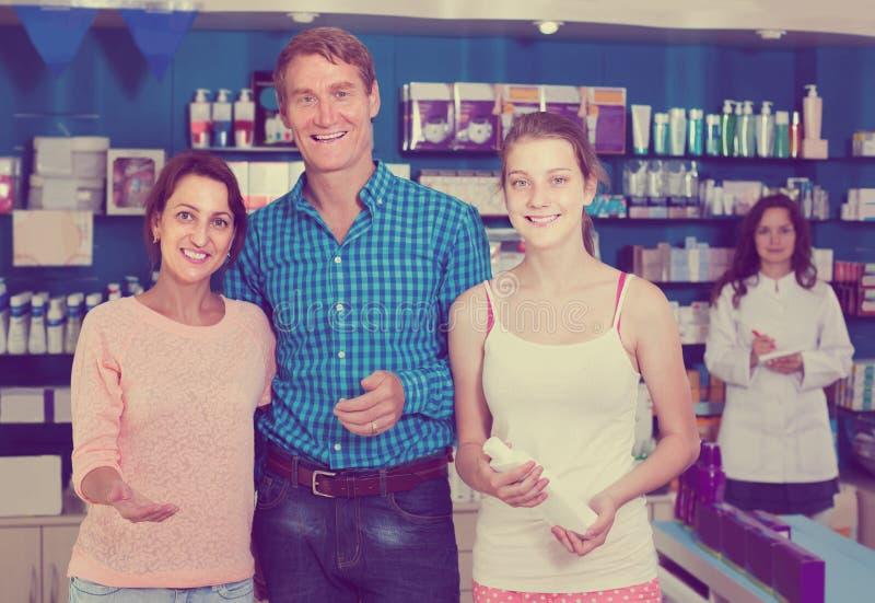Retrato dos pais com compra do adolescente da filha no stor da droga foto de stock royalty free