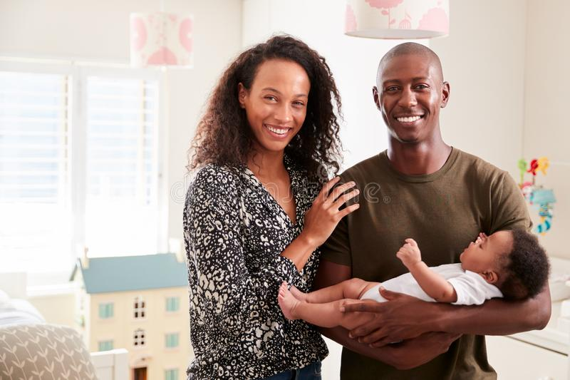 Retrato dos pais de amor que estão no filho de afago do bebê do berçário em casa foto de stock