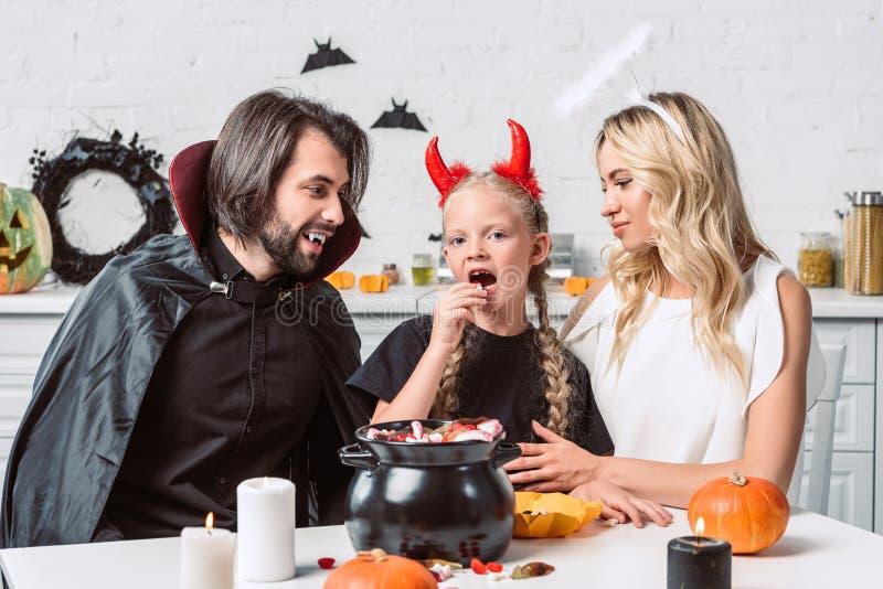 retrato dos pais e da filha em trajes do Dia das Bruxas na tabela com deleites no potenciômetro preto na cozinha imagens de stock royalty free