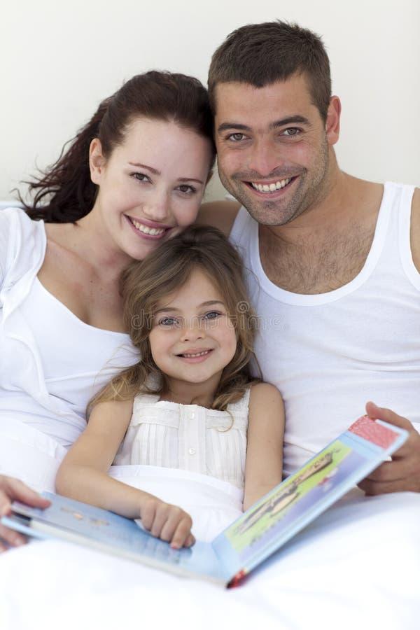 Retrato dos pais e da leitura da filha na cama imagem de stock royalty free