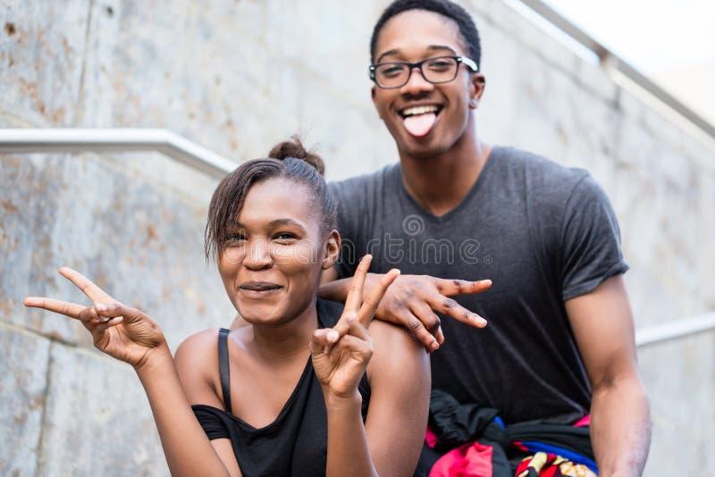 Retrato dos pares afro-americanos novos que fazem o whi engraçado das caras foto de stock